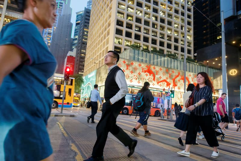 People cross a street the Central business district in Hong Kong