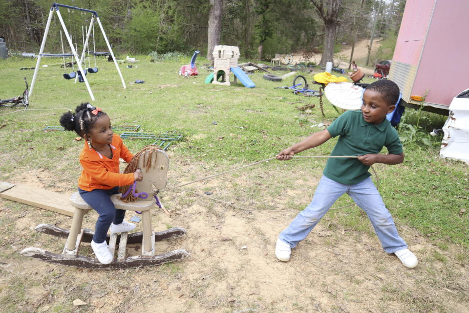 Keydon Turner, 6, plays with his 2-year-old sister, Kemiya, outside their home in Fayette, Miss. on Monday, March 22, 2021. (AP Photo/Leah Willingham)