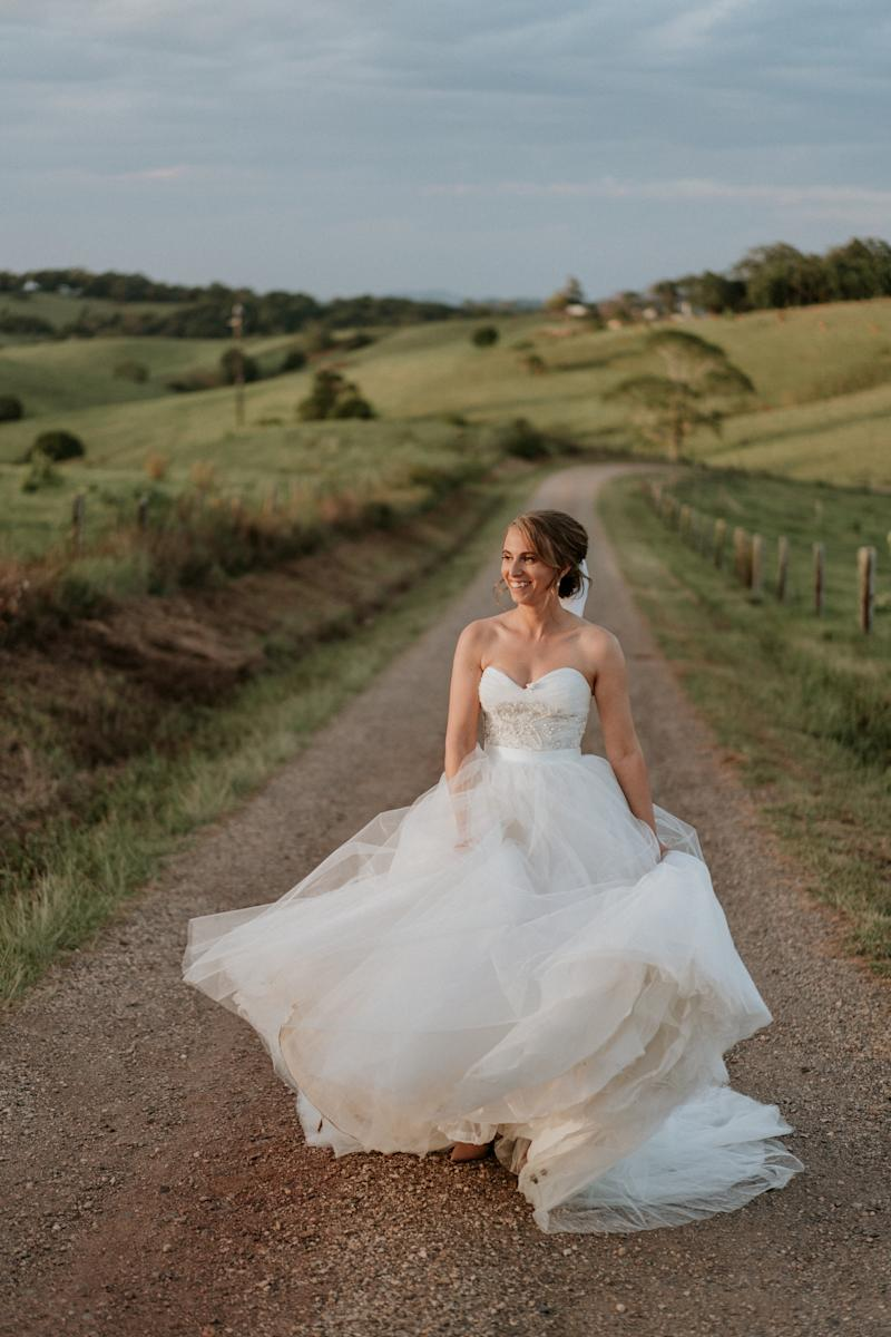 The bride, standing on a dirt road between green rolling hills, smiles as she plays with the skirt of her ball gown.  (James Day Photography)