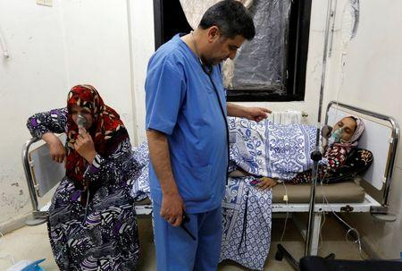 Women, affected by what activists say was a gas attack, receive treatment inside a makeshift hospital in Kfar Zeita village in Hama