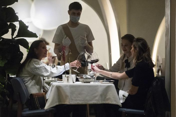 A waiter wearing a face mask and gloves to protect against coronavirus, serve customers in a restaurant at Patriarshiye Prudy, a hip restaurant and bar district in Moscow, Russia, late Friday, Oct. 16, 2020. The outbreak in Russia this month is breaking the records set in the spring, when a lockdown to slow the spread was put in place. But, as governments across Europe move to reimpose restrictions to counter rising cases, authorities in Russia are resisting shutting down businesses again. (AP Photo/Pavel Golovkin)