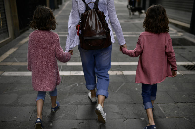 A family go for a walk taking their hands along a street of the old city, in Pamplona, northern Spain, Sunday, April 27, 2020. On Sunday, children under 14 years old will be allowed to take walks with a parent for up to one hour and within one kilometer from home, ending six weeks of compete seclusion. (AP Photo/Alvaro Barrientos)