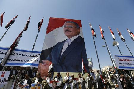 FILE PHOTO Supporters of Yemen's former President Ali Abdullah Saleh stand under a huge poster of Saleh as they rally in his support in Sanaa