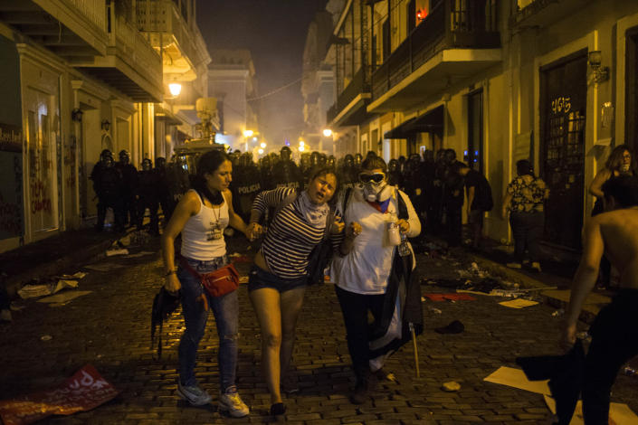 Demonstrators affected by tear gas thrown by the police run during clashes near the executive mansion demanding the resignation of Gov. Ricardo Rossello, in San Juan, Puerto Rico, Wednesday, July 17, 2019. (Photo: Dennis M. Rivera Pichardo/AP)