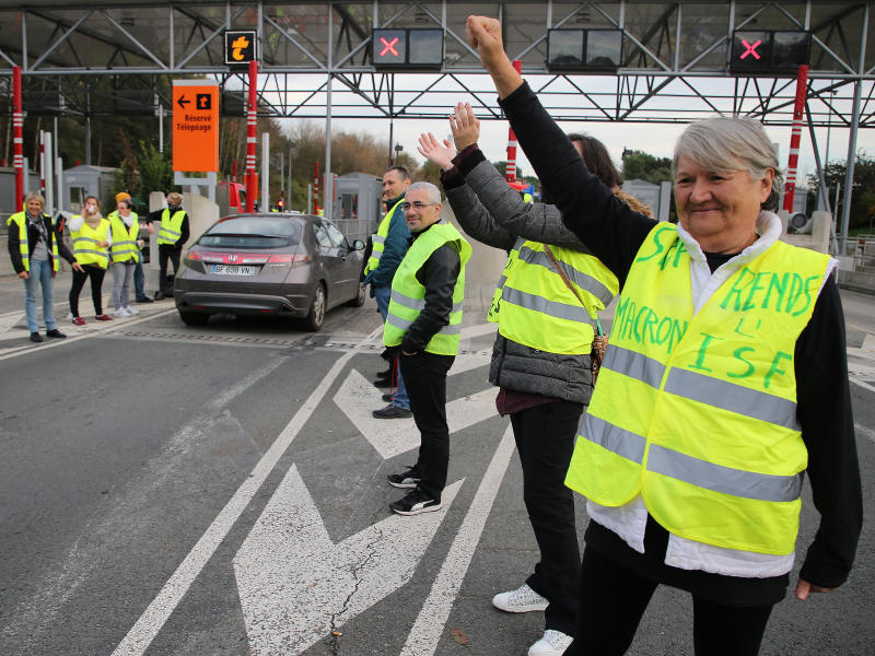 "A demonstrator wearing a yellow jacket reading "" Macron give us the wealth tax"" protests at the toll gates on a motorway at Biarritz southwestern France, Wednesday, Dec.5, 2018.The concessions made by French president Emmanuel Macron's government in a bid to stop the huge and violent anti-government demonstrations seemed on Wednesday to have failed to convince protesters, with trade unions and disgruntled farmers now threatening to join the fray.(AP Photo/Bob Edme)"