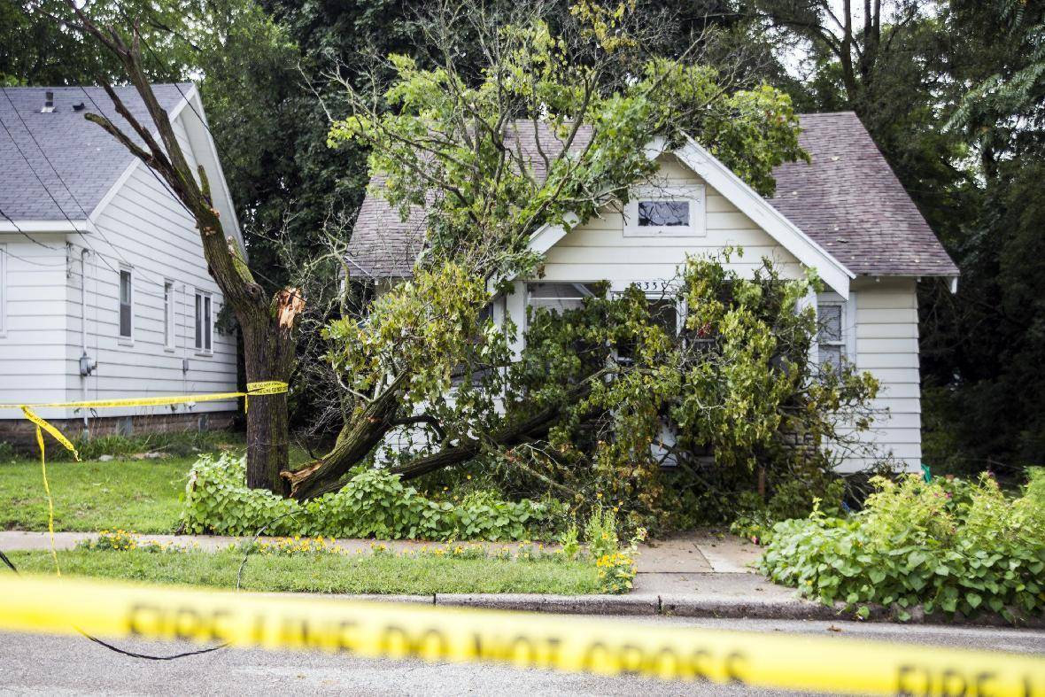 Tree limbs crashed through the front windows of a home on Palace Avenue as a reported tornado swept through Grand Rapids, Mich. and surrounding cities on Saturday, Aug. 20, 2016. Residents exited through the back of the home to find power lines down in the front yard. (Allison Farrand/The Grand Rapids Press via AP)