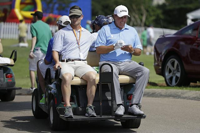 Phil Mickelson, right, fills out his scorecard as he rides from the 18th green to the first tee during the first round of the St. Jude Classic golf tournament Thursday, June 5, 2014, in Memphis, Tenn. (AP Photo/Mark Humphrey)