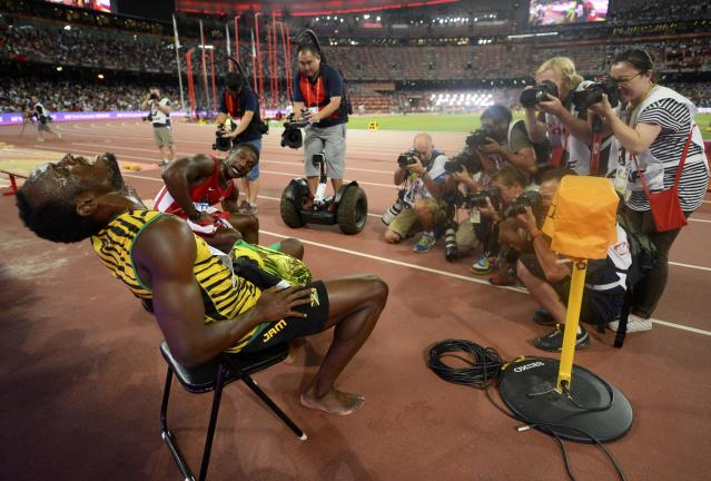 Usain Bolt of Jamaica poses for photographers after winning the men's 200 metres final during the 15th IAAF World Championships at the National Stadium in Beijing