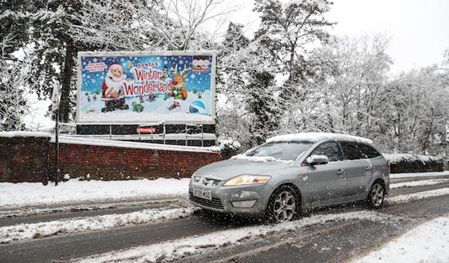 A car drives past a snow covered sign advertising Santa's Winter Wonderland in Worcester, as heavy snowfall across parts of the UK is causing widespread disruption, closing roads and grounding flights at an airport.