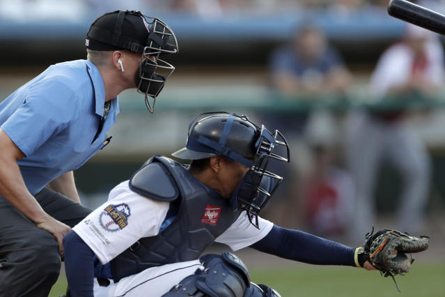 Home plate umpire Brian deBrauwere, left, huddles behind Freedom Division catcher James Skelton, of the York Revolution, as the official wears an earpiece during the first inning of the Atlantic League All-Star minor league baseball game, Wednesday, July 10, 2019, in York, Pa. deBrauwere wore the earpiece connected to an iPhone in his ball bag which relayed ball and strike calls upon receiving it from a TrackMan computer system that uses Doppler radar. The independent Atlantic League became the first American professional baseball league to let the computer call balls and strikes during the all star game. (AP Photo/Julio Cortez)