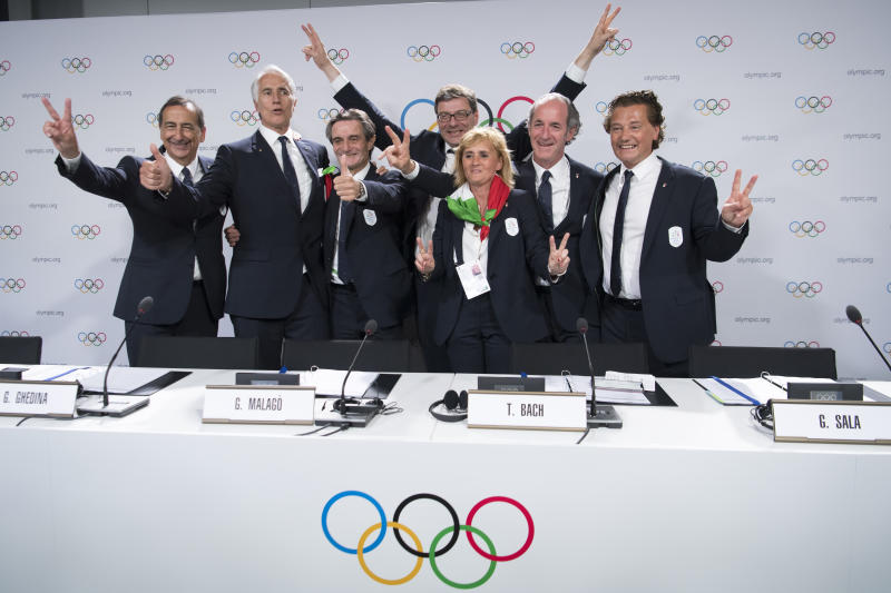 From left, the Mayor of Milan Giuseppe Sala, Italy's National Olympic Committee (CONI) president Giovanni Malago, Italy's Lombardy region President Attilio Fontana, Italy's Under Secretary of State Giancarlo Giorgetti, Italy's Olympic Gold Medallist in Fencing Diana Bianchedi, Italy's Veneto Region President Luca Zaia and Mayor of Cortina Gianpietro Ghedina pose after Milan-Cortina won the bid to host the 2026 Winter Olympic Games, during the first day of the 134th Session of the International Olympic Committee (IOC), at the SwissTech Convention Centre, in Lausanne, Switzerland, Monday, June 24, 2019. Italy will host the 2026 Olympics in Milan and Cortina d'Ampezzo, taking the Winter Games to the Alpine country for the second time in 20 years. (Laurent Gillieron/Keystone via AP)
