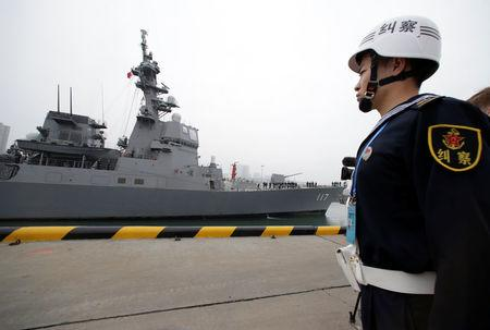 A Chinese navy personnel stands guard as the Japan Maritime Self-Defense Force destroyer JS Suzutsuki (DD 117) arrives at Qingdao Port for the 70th anniversary celebrations of the founding of the Chinese PLAN in Qingdao