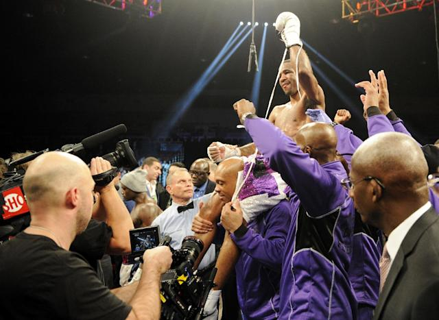 Lamont Peterson is lifted up in the ring after he beat Dierry Jean, of Canada, in the IBF Junior welterweight title boxing match, Saturday, Jan. 25, 2014, in Washington. (AP Photo/Nick Wass)