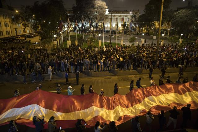 Demonstrators who had gathered to protest lawmakers pushing forward a vote to select an almost-full slate of new magistrates to the Constitutional Tribunal, continue outside Congress after President Martin Vizcarra dissolved the legislature in Lima, Peru, Monday, Sept. 30, 2019. Lawmakers were pushing forward the vote despite Vizcarra's warning that the move threatens his fight against corruption and that he would dissolve the opposition-controlled legislature. (AP Photo/Rodrigo Abd)