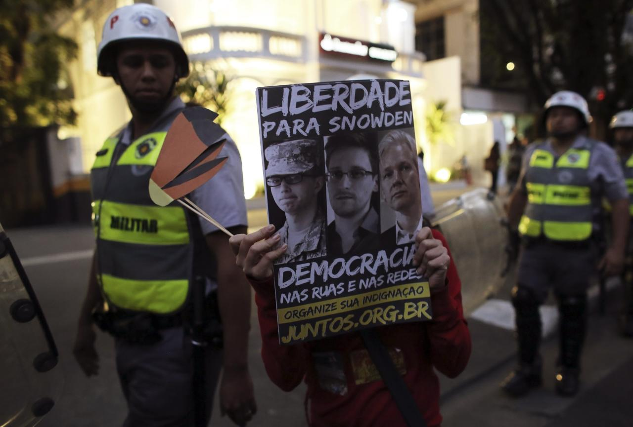 "A student of the University of Sao Paulo (USP) holds a poster bearing pictures of U.S. Army Private First Class Bradley Manning, former U.S. spy agency contractor Edward Snowden and Wikileaks founder Julian Assange (L-R) in front of military police during a protest against Sao Paulo State Governor Geraldo Alckmin, in Sao Paulo October 9, 2013. The banner reads ""Freedom to Snowden"" (top) and ""Democracy in the streets and social networks"". REUTERS/Nacho Doce (BRAZIL - Tags: POLITICS CIVIL UNREST EDUCATION)"