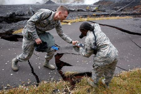 Senior Airman John Linzmeier and Technical Sergeant Alison Bruce-Maldonado of the Hawaii National Guard document road damage in Leilani Estates during ongoing eruptions of the Kilauea Volcano in Hawaii, U.S., May 18, 2018. REUTERS/Terray Sylvester