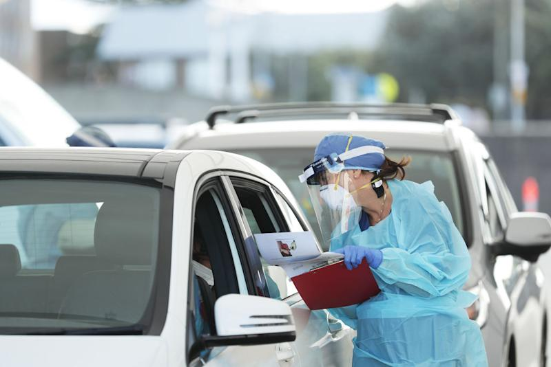 A medical professional leans into a car window to administer a COVID-19 test at the Bondi Beach drive-through COVID-19. Source: Getty