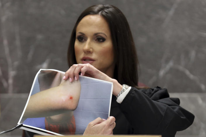 Judge Elizabeth Scherer holds a photograph of Parkland school shooter Nikolas Cruz showing an apparent injury to his elbow stemming from a November 2018 altercation between Cruz and Broward jail guard Sgt. Ray Beltran during Cruz's pre-trial hearing at the Broward County Courthouse in Fort Lauderdale, Fla., Wednesday, July 14, 2021, on four criminal counts stemming from his alleged attack. Cruz is accused of punching Sgt. Ray Beltran, wrestling him to the ground and taking his stun gun. (Amy Beth Bennett/South Florida Sun-Sentinel via AP, Pool)