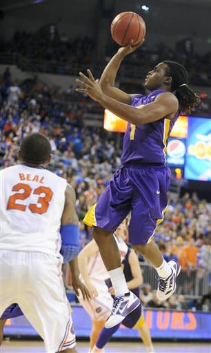 LSU's Anthony Hickey (1) goes for two points with Florida's Bradley Beal (23) not able to block the shot during the second half of an NCAA college basketball game in Gainesville, Fla., Saturday, Jan. 21, 2012. Florida defeated LSU 76-64. (AP Photo/Phil Sandlin)