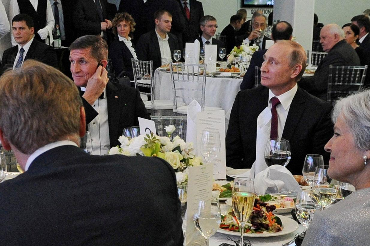Russian President Vladimir Putin, right, sits next to retired U.S. Army Lt. Gen. Michael Flynn at an event marking the 10th anniversary of RT (Russia Today) in Moscow in 2015. (Sputnik/Mikhail Klimentyev/Kremlin via Reuters)