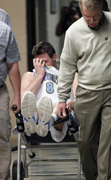 Denver Nuggets forward Danilo Gallinari, of Italy, uses his jersey to cover his face as he is wheeled to the locker room by the team's head trainer Jim Gillen, front, after being injured against the Dallas Mavericks in the second quarter of an NBA basketball game in Denver on Thursday, April 4, 2013. (AP Photo/David Zalubowski)
