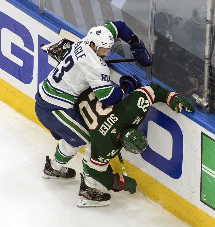 Minnesota Wild's Ryan Suter (20) is checked by Vancouver Canucks' Jay Beagle (83) during the first period in an NHL hockey game in Edmonton, Alberta, Thursday Aug. 6, 2020. (Jason Franson/The Canadian Press via AP)