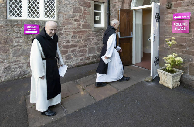 Monks Father Leonard Norman, left, and Father Mark Caira from the Sancta Maria Abbey in Garvald, Scotland, arrive at a polling station to cast their votes for the European Parliamentary election. (Jane Barlow/PA via AP)