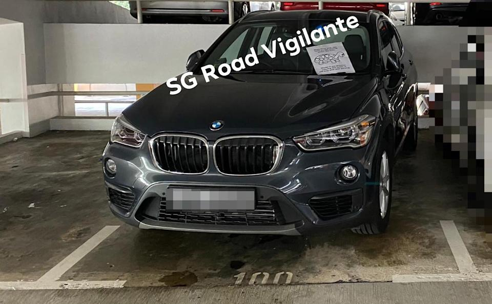 A BMW SUV parked crookedly with a note on the windshield.