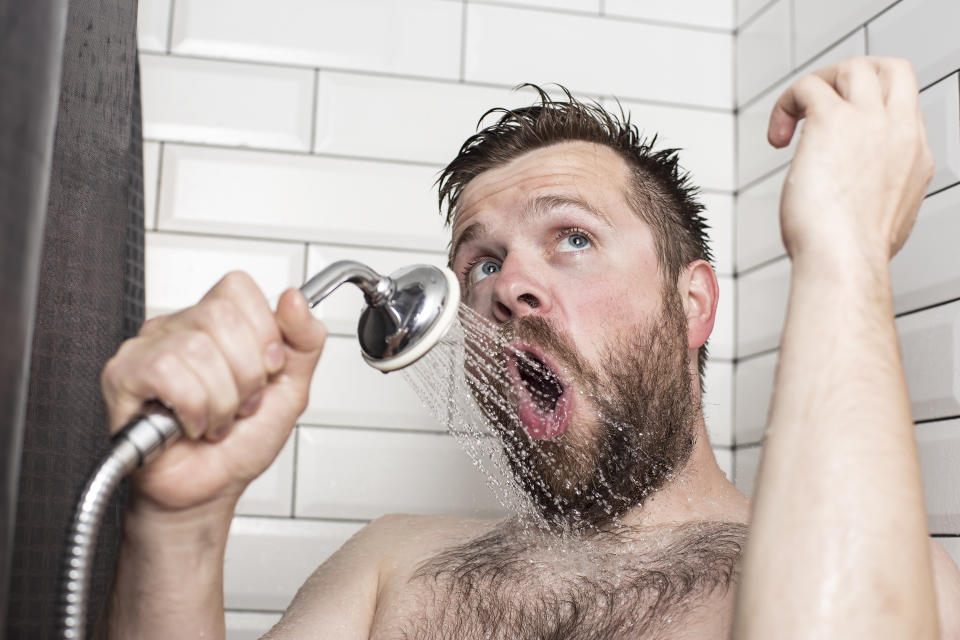 Cute bearded man singing in the bathroom using the shower head with flowing water instead of a microphone. Close-up.