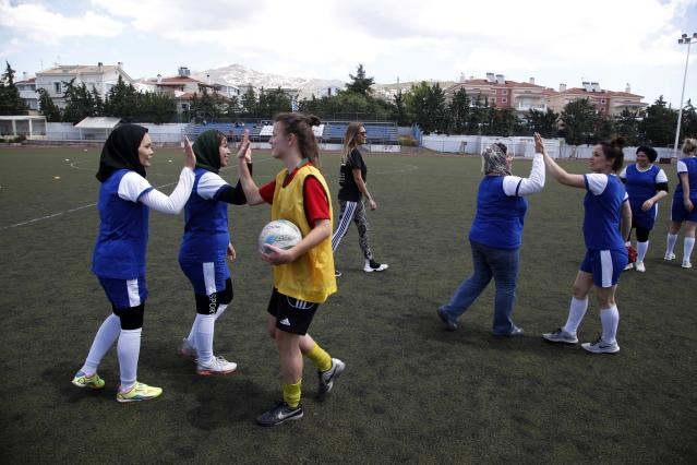 In this Thursday, May 2, 2019 photo, members of Hestia FC Women's Refugee Soccer and AO Vrilission players shake hands after a friendly game in Athens. Many of the players at Hestia FC weren't allowed to play or even watch soccer matches in their home countries. Hestia FC was set up by the Olympic Truce Centre, a non-government organization created in 2000 by the International Olympic Committee and Greek Foreign Ministry. (AP Photo/Thanassis Stavrakis)
