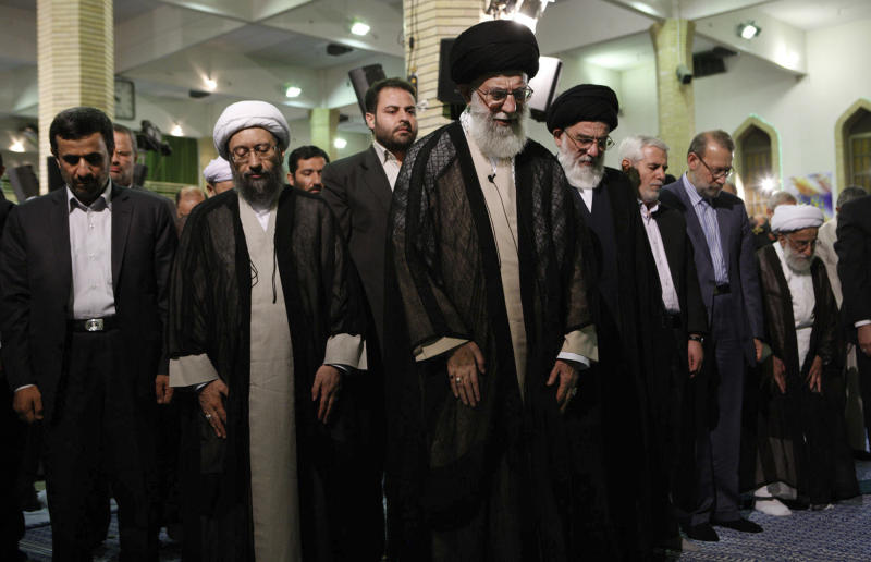 In this photo released by the official website of the Iranian supreme leader's office and taken on Tuesday, July 24, 2012, Iranian supreme leader Ayatollah Ali Khamenei, center, leads prayer, in Tehran, Iran. Iran's Supreme Leader says Western-led sanctions and pressure will not force Iran to change its policies, voicing confidence that the country can beat the latest moves to block its vital oil and banking industries. Iranian President Mahmoud Ahmadinejad prays at, left, and judiciary chief Ayatollah Sadeq Larijani, second left. (AP Photo/Office of the Supreme Leader)