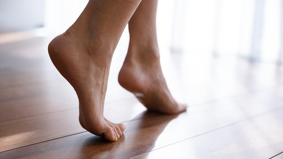 Close up side view beautiful female feet with perfect smooth skin standing tiptoe on warm wooden floor with underfloor heating, barefoot young woman walking at home, enjoying morning, relaxing