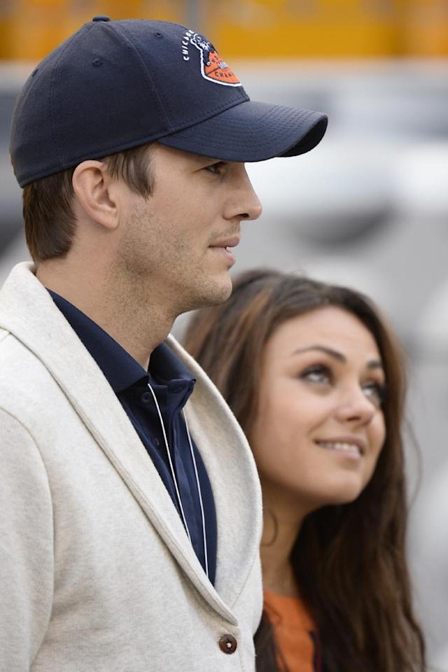 Ashton Kutchar, left, and Mila Kunis walk along the sideline before the NFL football game between the Pittsburgh Steelers and the Chicago Bears at Heinz Field on Sunday, Sept. 22, 2013, in Pittsburgh. (AP Photo/Keith Srakocic)