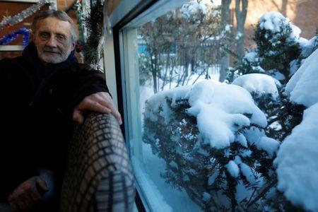 Tom Smith, who is homeless, sits for a portrait inside the Pine Street Inn, with snow covering the bushes outside, in Boston, Massachusetts, U.S., January 5, 2018. REUTERS/Brian Snyder