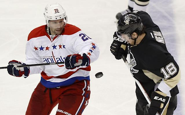Pittsburgh Penguins' James Neal (18) and Washington Capitals' Troy Brouwer (20) try to control the puck as it flies by during the third period of an NHL hockey game, Tuesday, March 11, 2014, in Pittsburgh. The Penguins won 2-0. (AP Photo/Keith Srakocic)