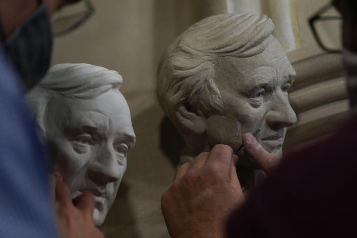 Artist Chas Fagan, left, works to fine tune his sculpture of Holocaust survivor and Nobel Peace Prize winning author Elie Wiesel with stone carver Sean Callahan in the Human Rights Porch of the Washington National Cathedral, Friday, April 16, 2021. (AP Photo/Carolyn Kaster)