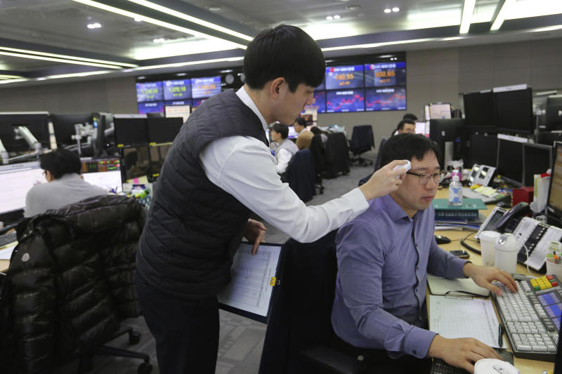 A currency trader checks the temperature of his colleague at the foreign exchange dealing room of the KEB Hana Bank headquarters in Seoul, South Korea, Thursday, Feb. 20, 2020. Asian shares were mixed Thursday after Wall Street recovered to record highs, but worries continued about the damage to the regional economy from the new virus that began in China. (AP Photo/Ahn Young-joon)