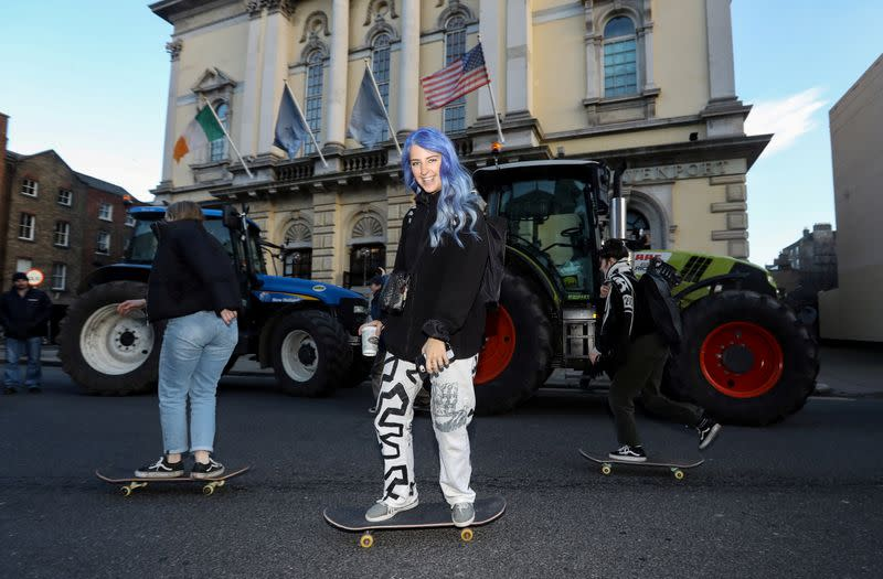 Skateboarders avoid the traffic jam caused by farmers' protest near Government Buildings in Dublin