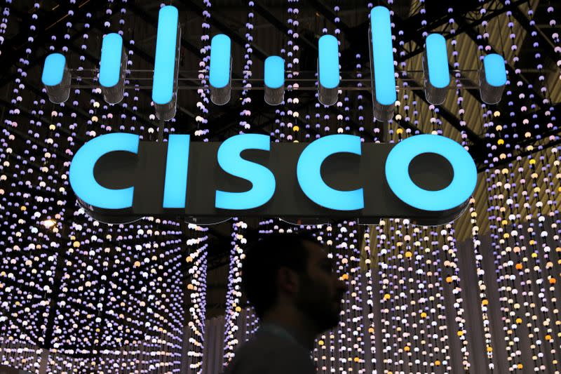 A man passes under a Cisco logo at the Mobile World Congress in Barcelona