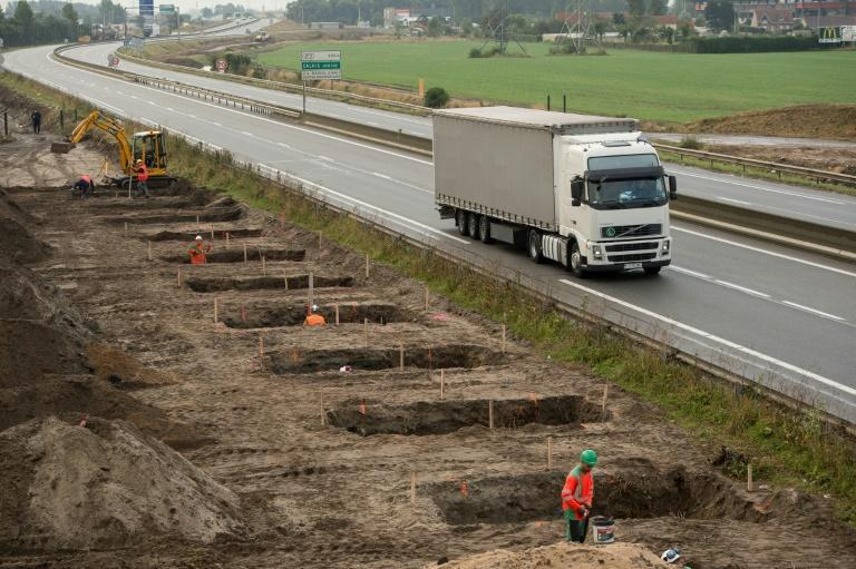Workers dig foundations of a wall near the Calais migrant camp along the road leading to the harbour to stop migrants from jumping on lorries bound for Britain
