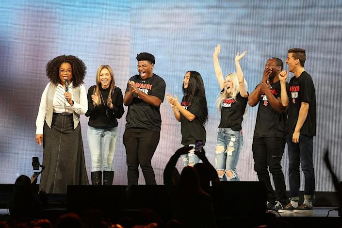 """DALLAS, TX – FEBRUARY 15: Oprah Winfrey speaks with the cast of Netflix's """"Cheer"""", (L-R) Monica Aldama, Jerry Harris, Gabi Butler, Lexi Brumback, TT Barker and Dillon Brandt during Oprah's 2020 Vision: Your Life in Focus Tour presented by WW (Weight Watchers Reimagined) at American Airlines Center on February 15, 2020 in Dallas, Texas. (Photo by Omar Vega/Getty Images)"""