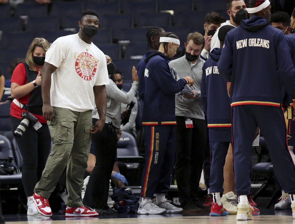 New Orleans Pelicans forward Zion Williamson, front left, watches from the sideline in the first half of an NBA preseason basketball game against the Minnesota Timberwolves, Monday, Oct. 4, 2021, in Minneapolis. (AP Photo/Andy Clayton-King)