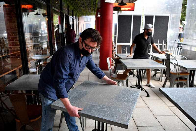 Workers setup tables for outdoor dining at Sambandha Nepalese restaurant at Auburn in Sydney.
