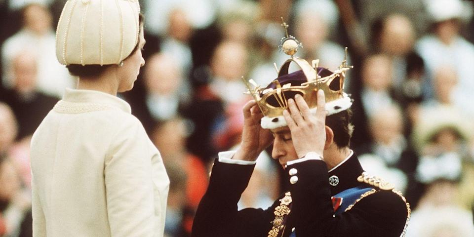 <p>Kneeling before Queen Elizabeth II as she crowns him Prince of Wales at the investiture with a gold crown.</p>