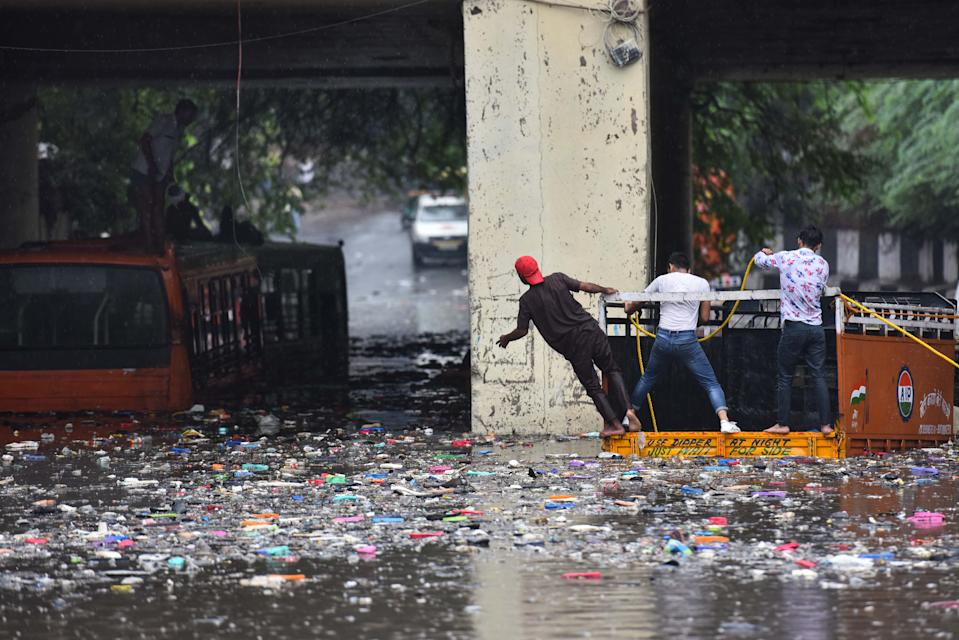 Rescue work underway to retrieve people trapped in buses that got stuck in water that collected under the Zakhira bridge after heavy rainfall, on July 19, 2020 in New Delhi, India. Moderate-to-heavy rain lashed several states in northern, eastern and coastal India on Sunday, but the monsoon activity continued to remain subdued in Delhi, which has recorded a 40 per cent rainfall deficiency despite an early onset of the seasonal weather system. (Photo By Sanchit Khanna/Hindustan Times via Getty Images)