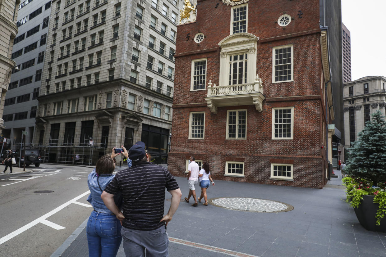 BOSTON - JULY 3: Tourists take a picture of the Old State House, a Boston landmark, on July 3, 2020. On the eve of Fourth of July, crowds were sparse in front of the Old State House as a result of the coronavirus restricting travel. (Photo by Erin Clark/The Boston Globe via Getty Images)