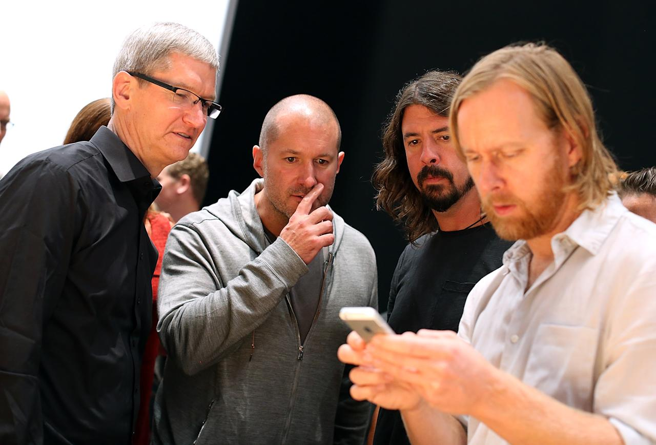 SAN FRANCISCO, CA - SEPTEMBER 12:  (L-R) Apple CEO Tim Cook, Apple senior vice president of Industrial Design Jonathan Ive and Dave Grohl of the Foo Fighters look on as an attendee looks at the new iPhone 5 during an Apple special event at the Yerba Buena Center for the Arts on September 12, 2012 in San Francisco, California. Apple announced the iPhone 5, the latest version of the popular smart phone.  (Photo by Justin Sullivan/Getty Images)