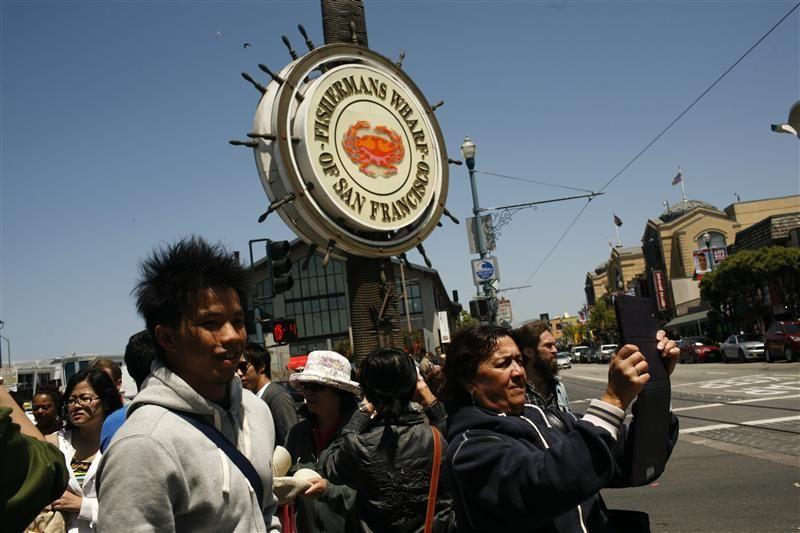 Tourists snap pictures at Fisherman's Wharf in San Francisco, California.