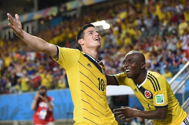 Colombia's midfielder James Rodriguez (L) celebrates with his teammate defender Pablo Armero after scoring at the Pantanal Arena in Cuiaba during the 2014 FIFA World Cup on June 24, 2014 (AFP Photo/Toshifumi Kitamura)