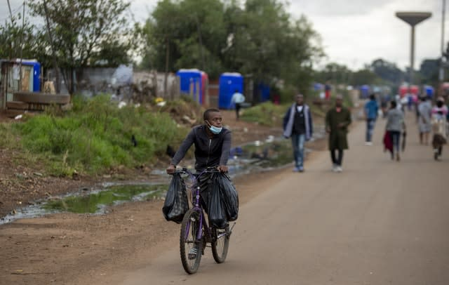 A man wearing a face mask to protect against coronavirus cycles in Thokoza, east of Johannesburg